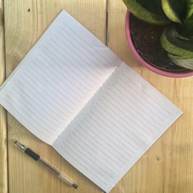 An open notebook with a pen next to it, ready to write and a plant in the background.