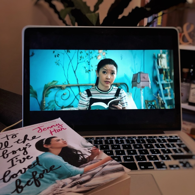 The film version of Lara Jean is displayed on a laptop, with the book on top of the keyboard in the foreground