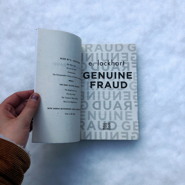 Genuine Fraud by E.Lockhart being held open on the title page, with a backdrop of crisp, icy snow.