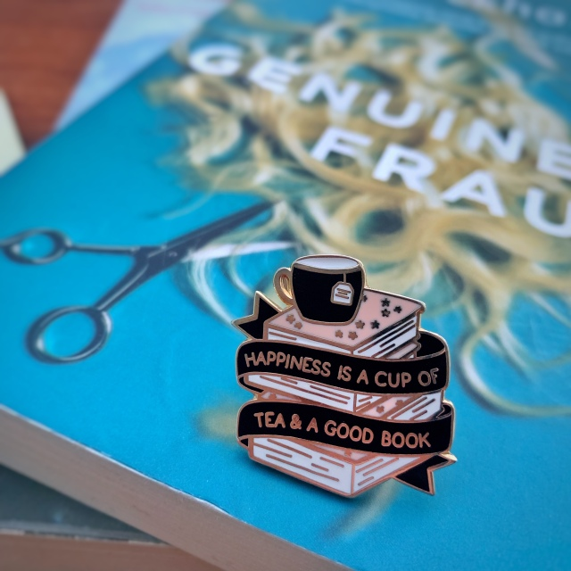 An enamel pin saying 'Happiness is a cup of tea & a good book', on top of Genuine Fraud. It emits cosy vibes.