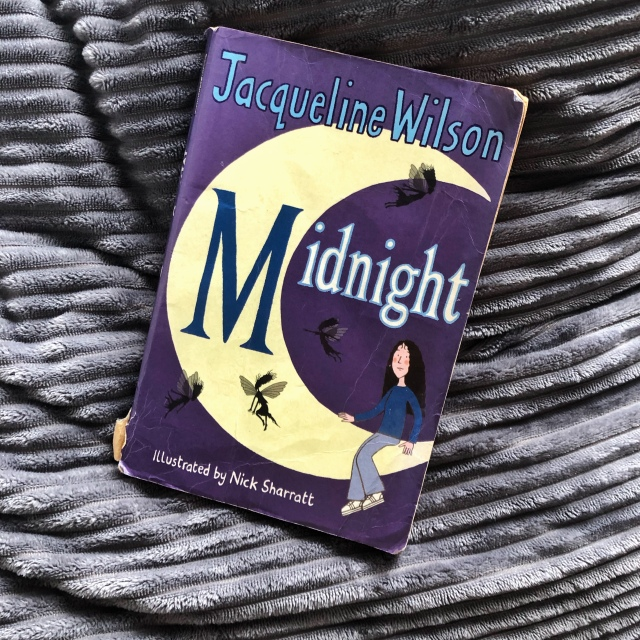 Midnight by Jacqueline Wilson on top of a dark grey ruffled pillow.