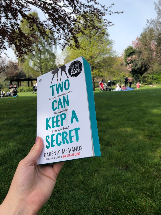Two can keep A Secret by karen McManus held up in a sunny park.