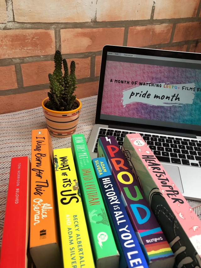 a selection of rainbow coloured books in front of a laptop with the bi pride flag stating 'A month of watching LGBTQ+ films for pride month'.